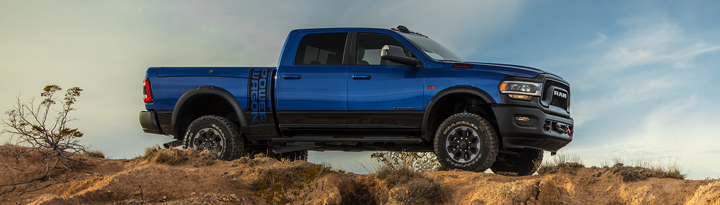 Side view of the new 2019 Ram 2500 blue parked outside at the top of a hill